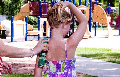 Young girl being sprayed with bug repellant